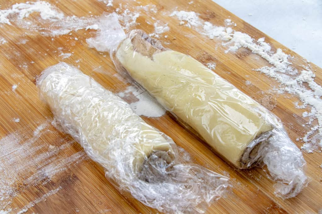 cinnamon roll cookie dough cut in half and wrapped in plastic wrap