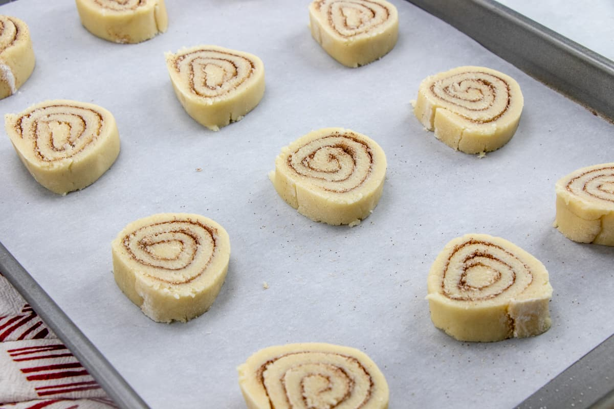 sliced cinnamon roll cookie dough on parchment paper covered baking sheet.
