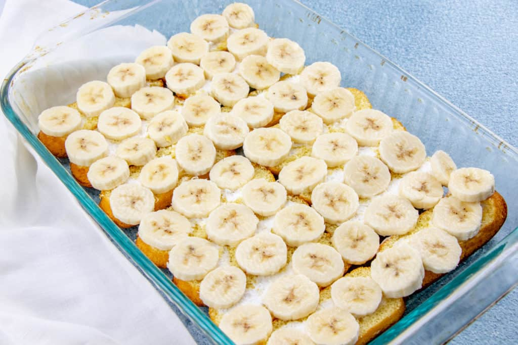 sliced fresh bananas on top of sliced Twinkies in a baking pan