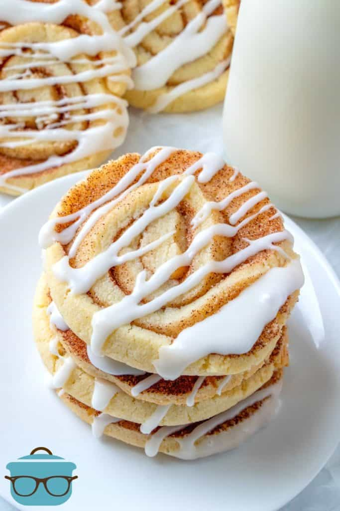 Cinnamon Roll Cookies stacked on a white plate served with a bottle of cold milk.