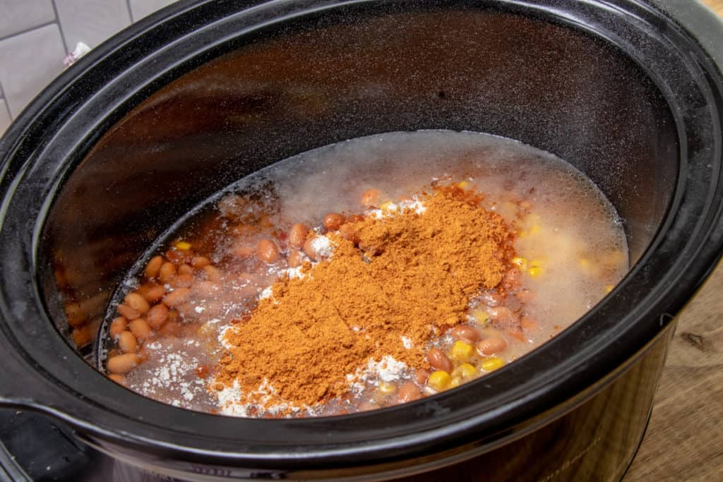 cooked ground beef, onions, diced tomatoes, corn, pinto beans and beef broth poured into 6-quart slow cooker
