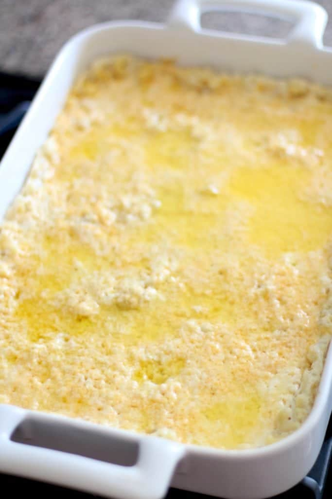 cooked elbow macaroni noodles, butter and cheese in a baking dish