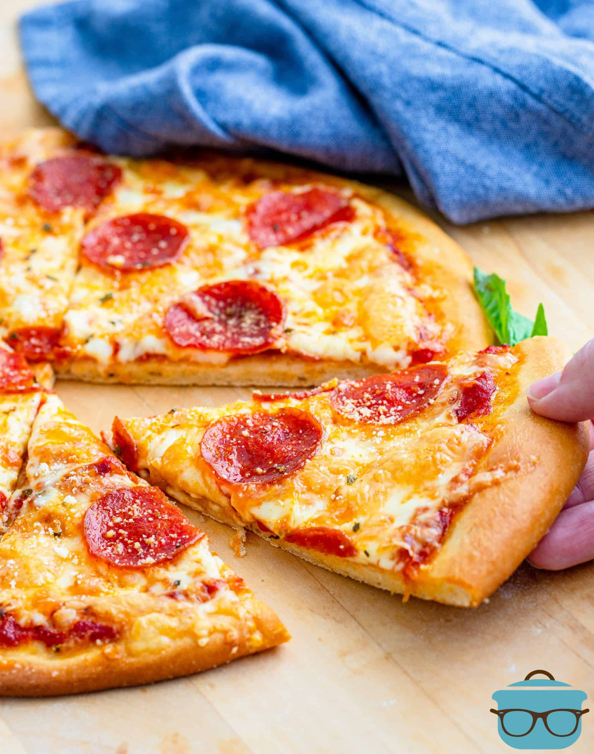 whole pepperoni pizza shown on a wooden board with one slice being removed.