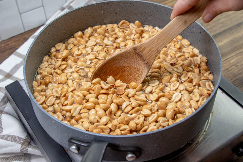 peanuts addd to sauce pan with sugar water and stirred with a wooden spoon