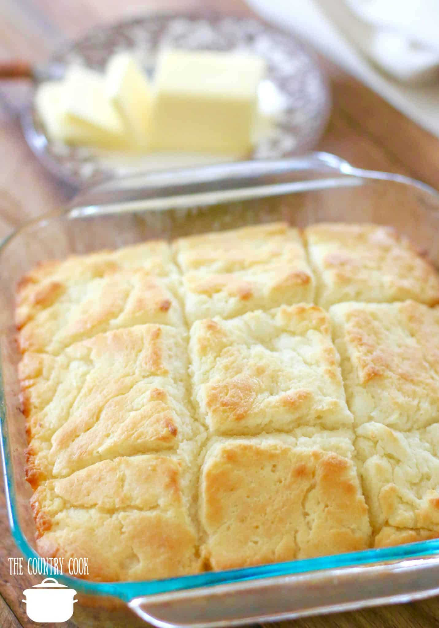 Butter Dip Buttermilk Biscuits recipe, no biscuit cutters, in a square Puree baking dish with sliced butter in the background.