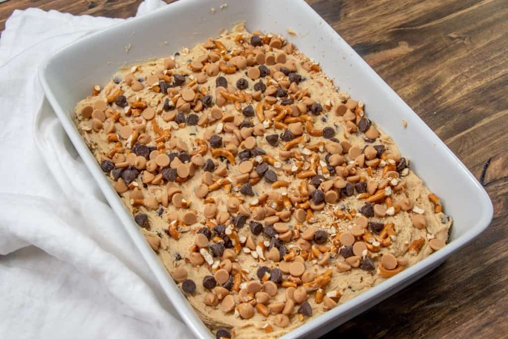 pretzel chocolate chip mixture sprinkled over raw cookie dough batter in a ceramic baking dish