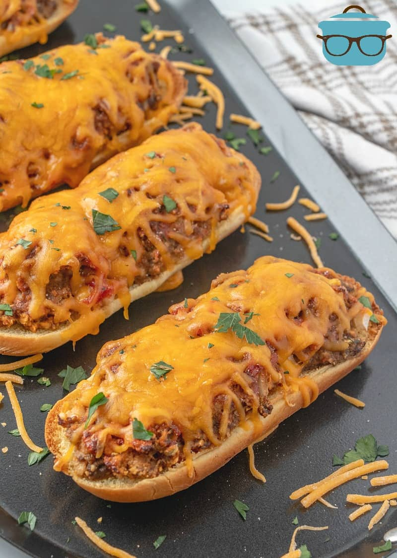 Meatloaf Patty Melts shown fully cooked on a dark silver serving tray sprinkled with shredded cheese and fresh parsley.