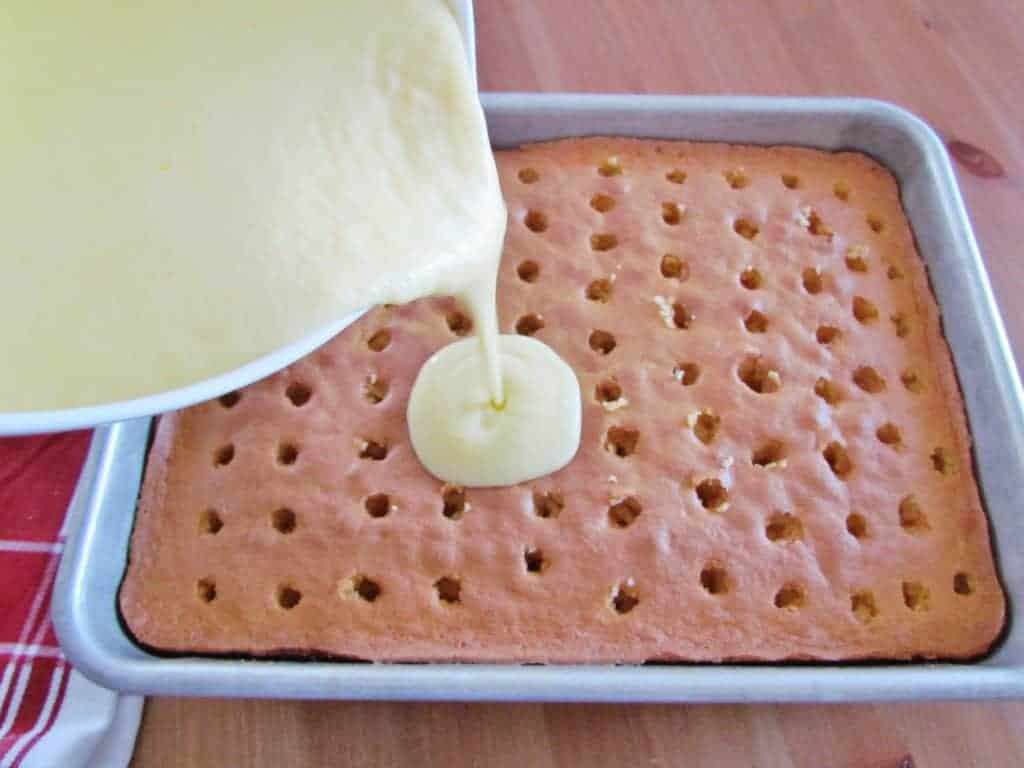 pouring prepared pudding into holes of baked yellow cake
