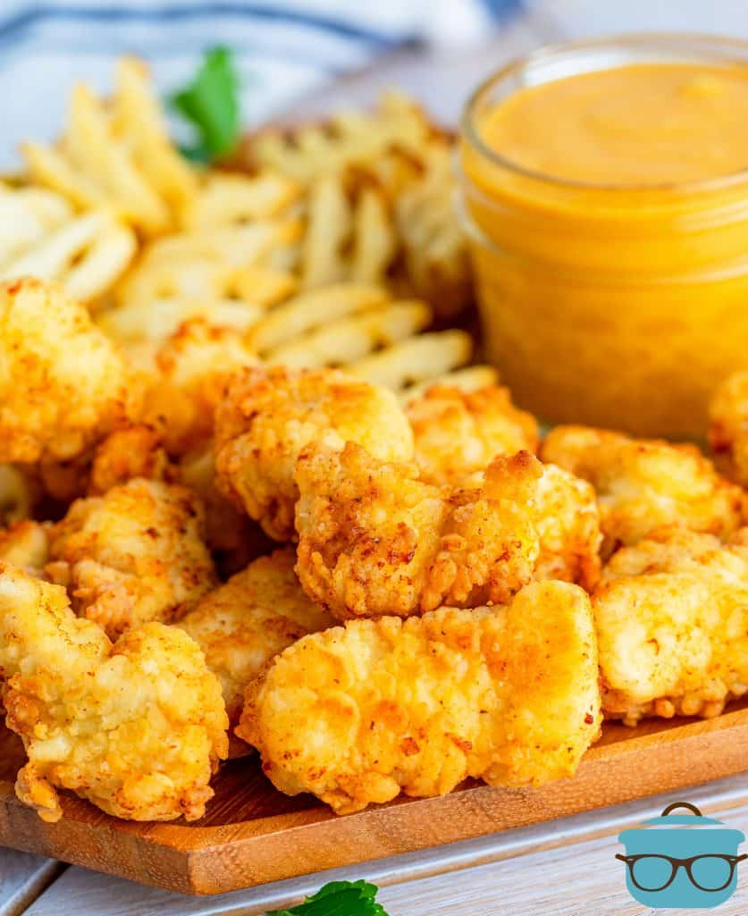 Copycat Chick-fil-A chicken nuggets ona plate with waffle fries and a small jar of honey mustard