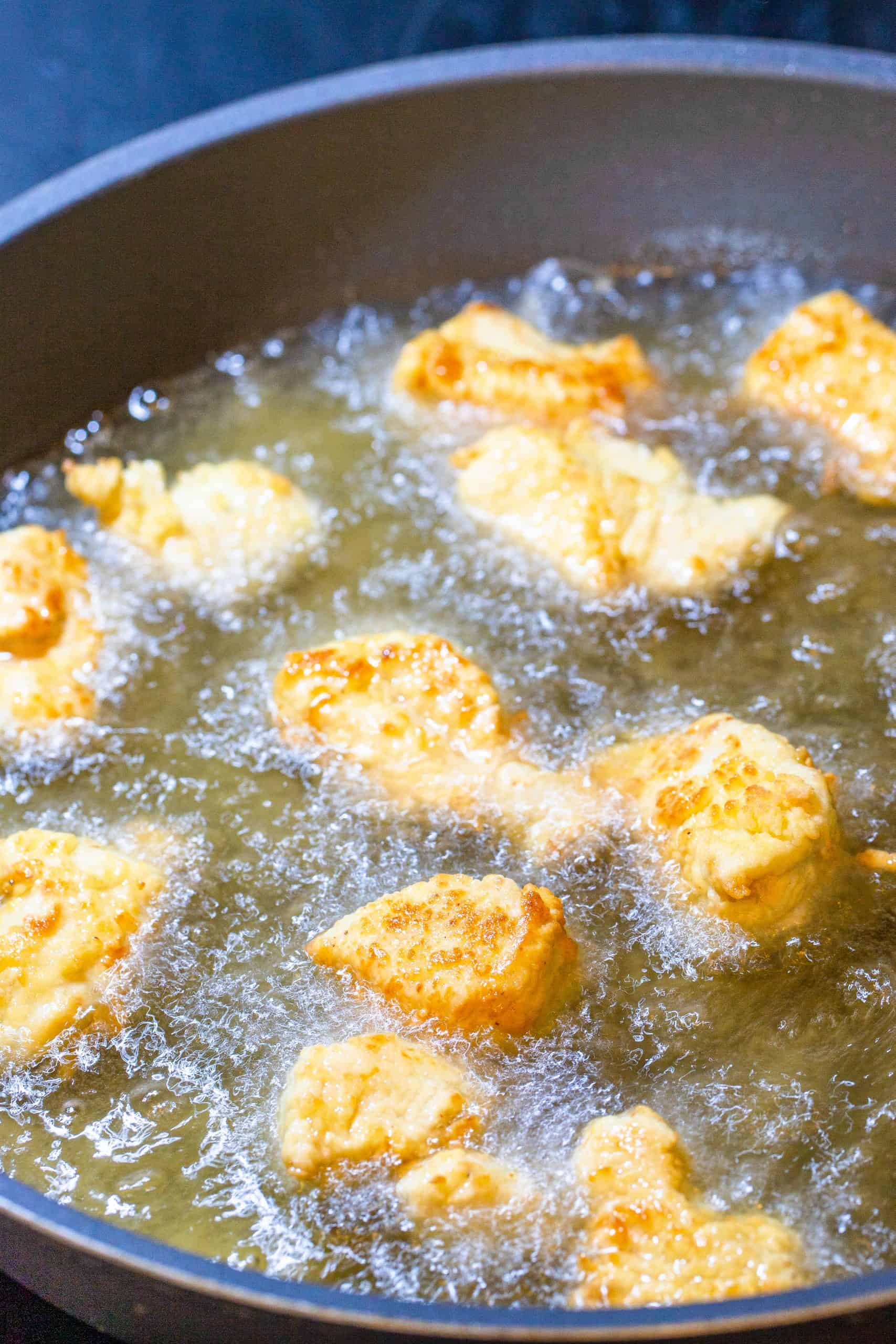 frying chicken nuggets in cast iron pan.