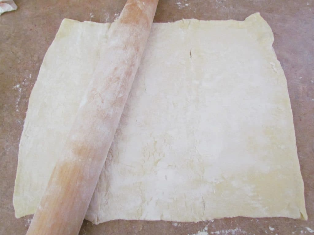 long rolling pin rolling out puff pastry on kitchen counter
