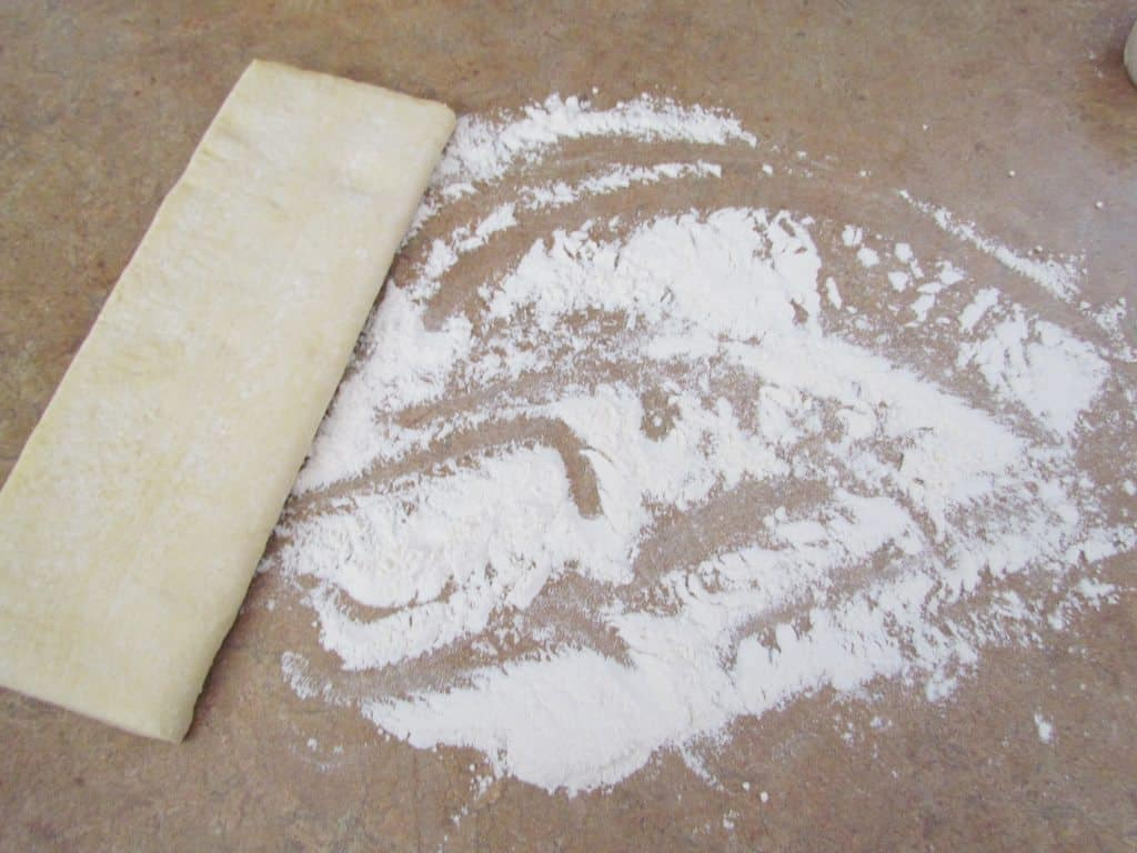 thawed puff pastry on a counter sprinkled with all-purpose flour