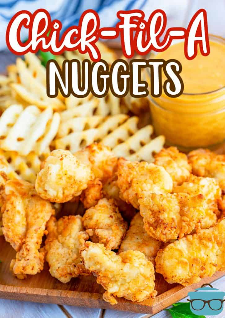 Copycat Chick-fil-A Chicken Nuggets shown on a wooden platter with waffle fries and honey mustard