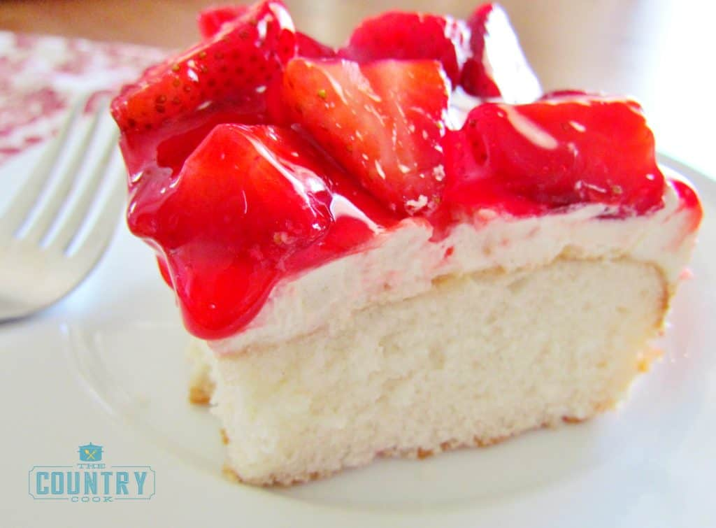 close up, slice of white cake with sweetened cream cheese and fresh strawberries with glaze