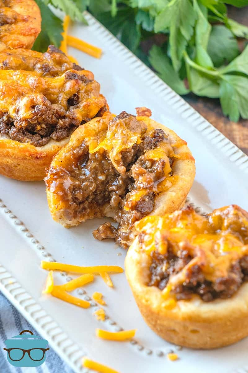 BBQ Beef Biscuit Cups topped with melted cheese displayed on a white tray.
