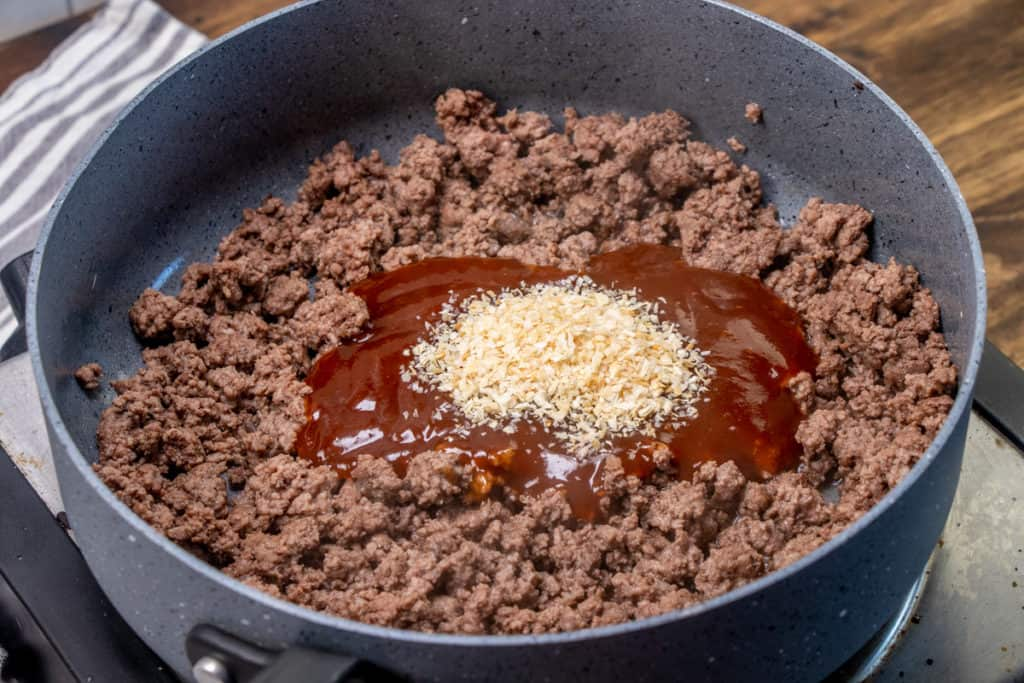 cooked ground beef in a large skillet with dried minced onions and barbecue sauce
