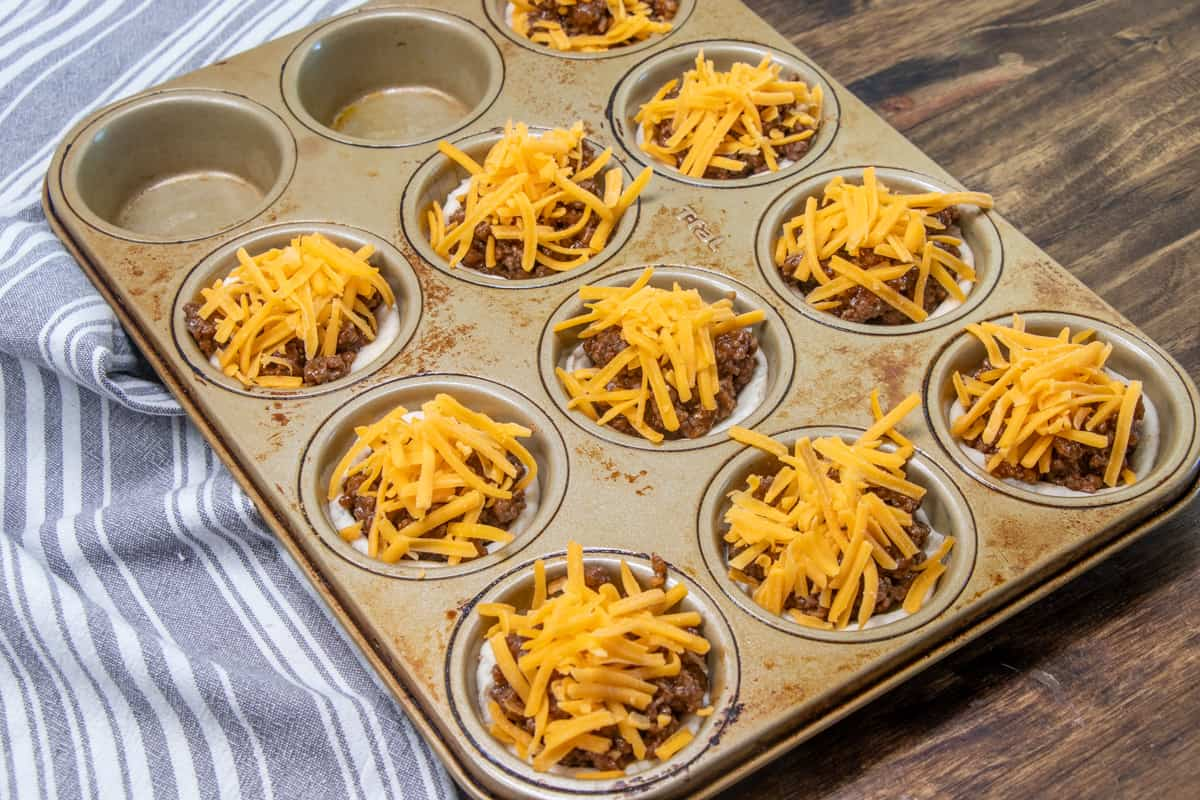 shredded cheese placed on top of bbq beef mixture in muffin pan.
