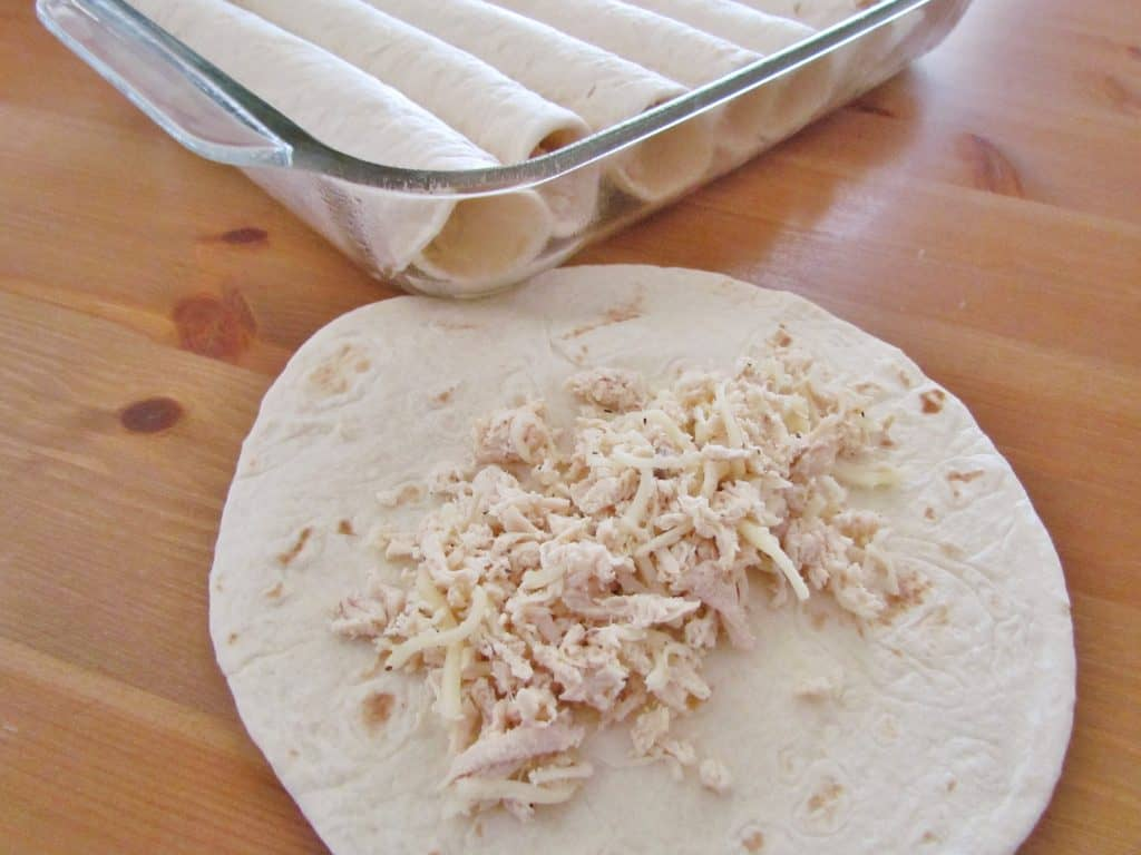chicken enchilada mixture in a flour tortilla