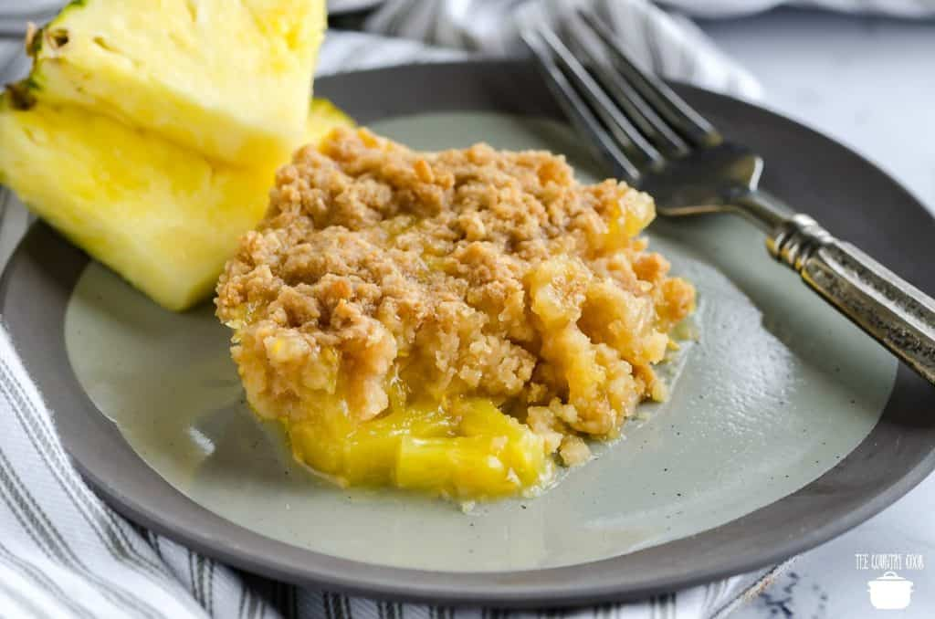 Warm Southern Pineapple Casserole on a plate with fresh pineapple