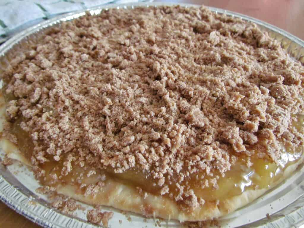 brown sugar crumble topping sprinkled over apple pie filling on pizza crust