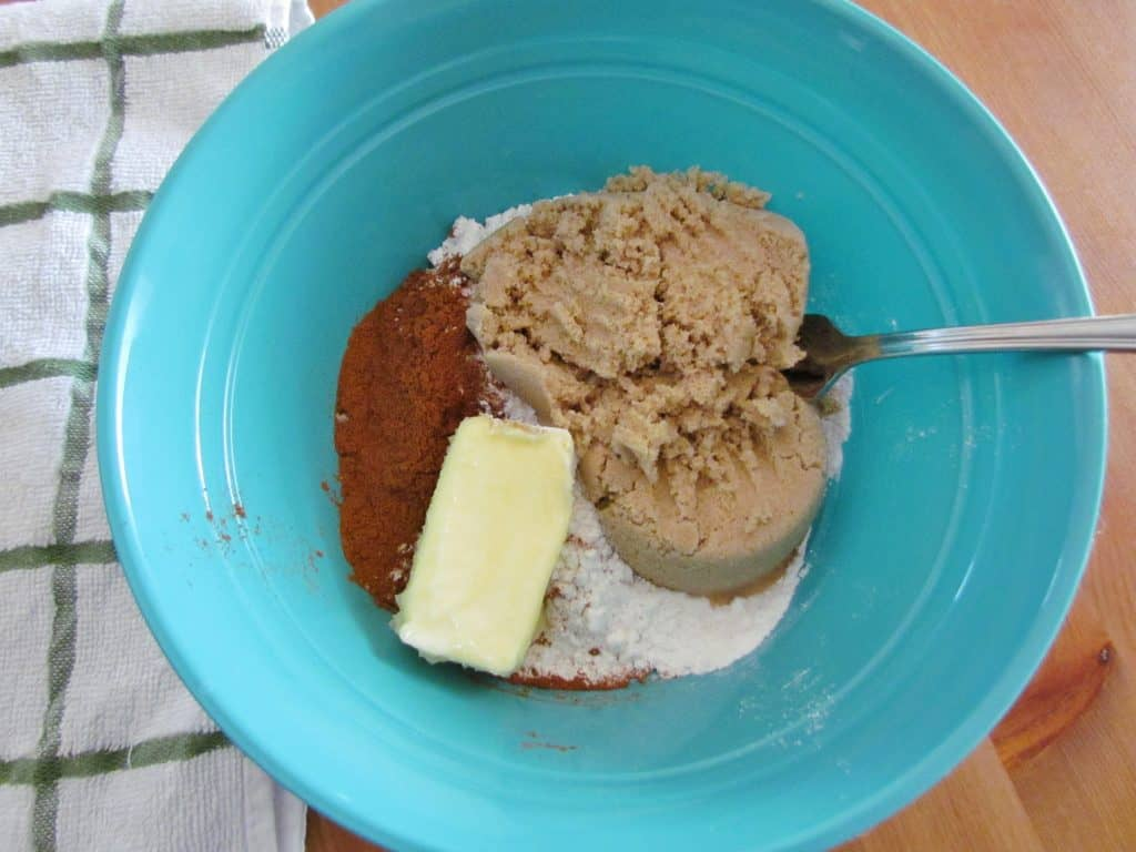 butter, brown sugar, flour and ground cinnamon in a blue mixing bowl with a fork
