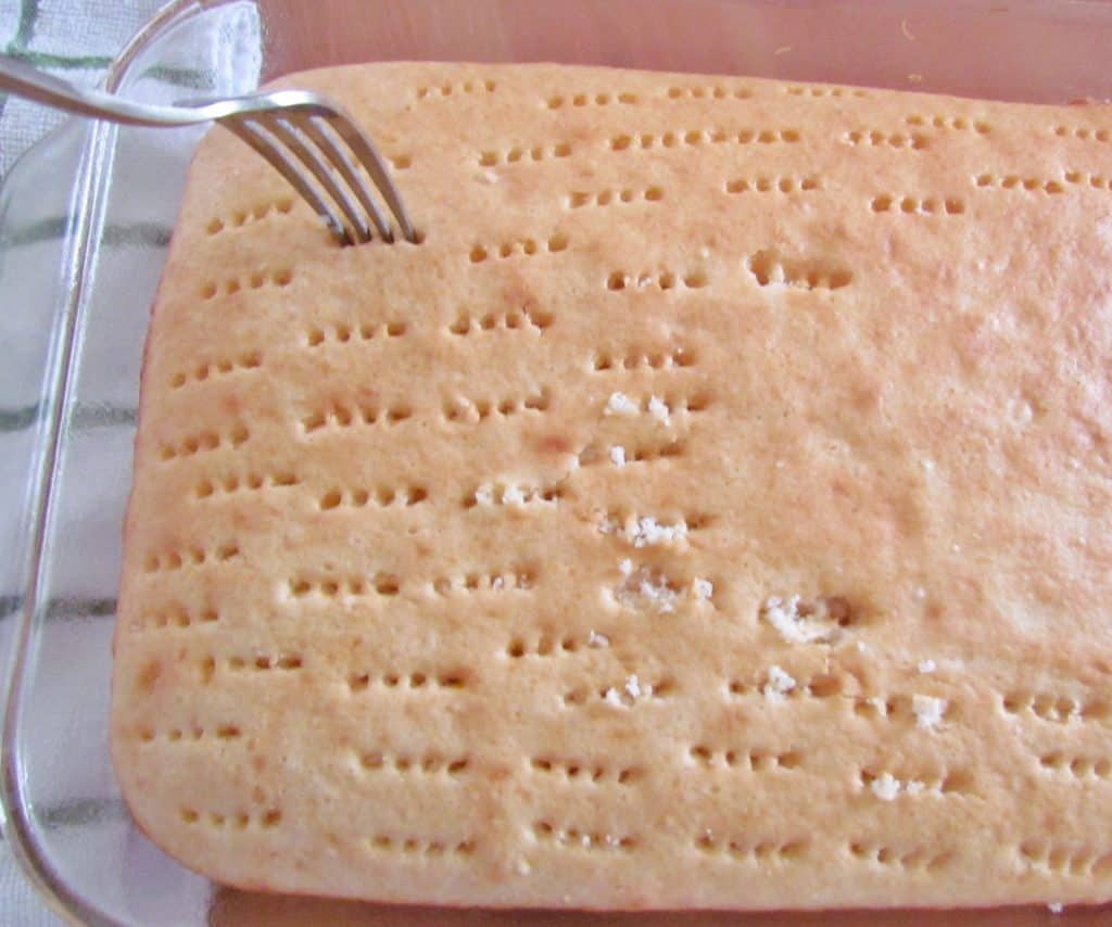 using a fork to poke holes into baked white cake
