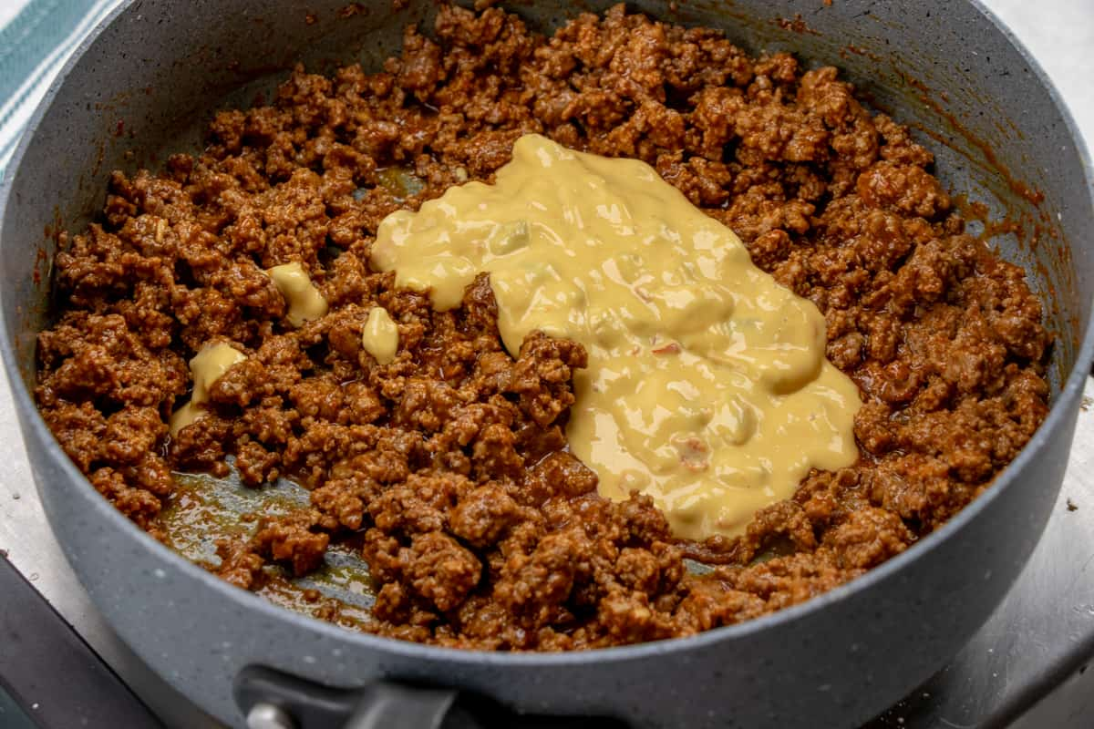 salsa con queso stirred into taco ground beef mixture in a saute pan