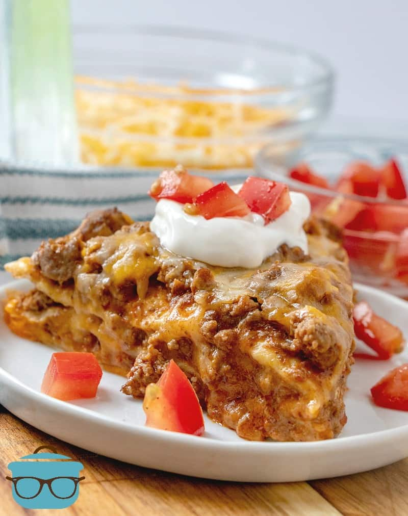 closeup, slice, taco bake topped with sour cream and tomatoes