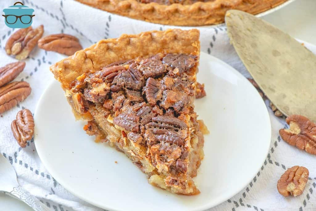 slice, homemade pecan pie on a white plate