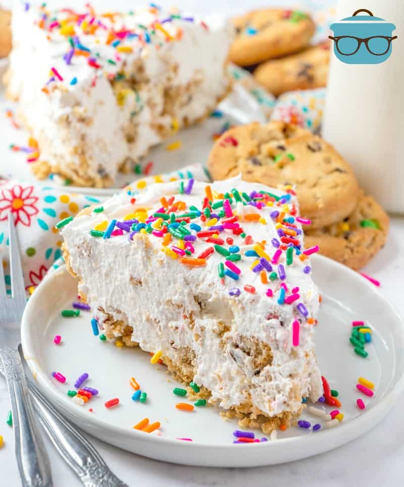 slices of Cookies and Cream Pie on plates, topped with sprinkles with a bottle of milk and cookies in the background