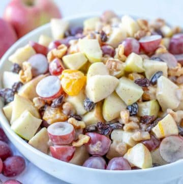 Creamy Cinnamon Apple Fruit Salad in a large bowl displayed with grapes and apples