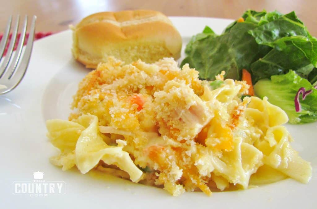 Chicken Noodle Casserole serving on a plate with salad and bread roll