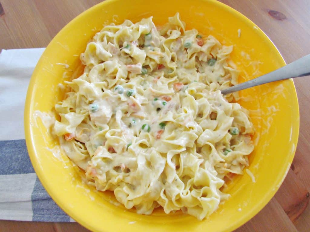 egg noodles stirred in with creamy filling mixture in a bowl