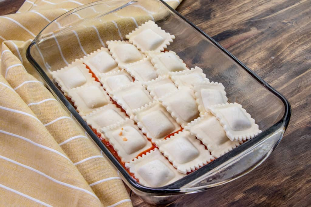 a layer of pasta sauce on the bottom of a clear 11-inch by 7-inch baking dish topped with a layer of frozen ravioli
