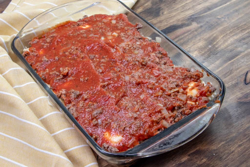 a layer of pasta sauce on top of cooked ground beef and frozen ravioli in a Pyrex glass baking dish