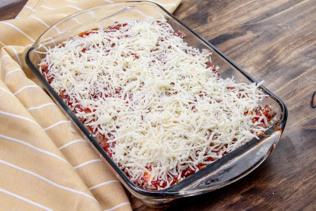 shredded cheese added on top of ravioli casserole layers in baking dish