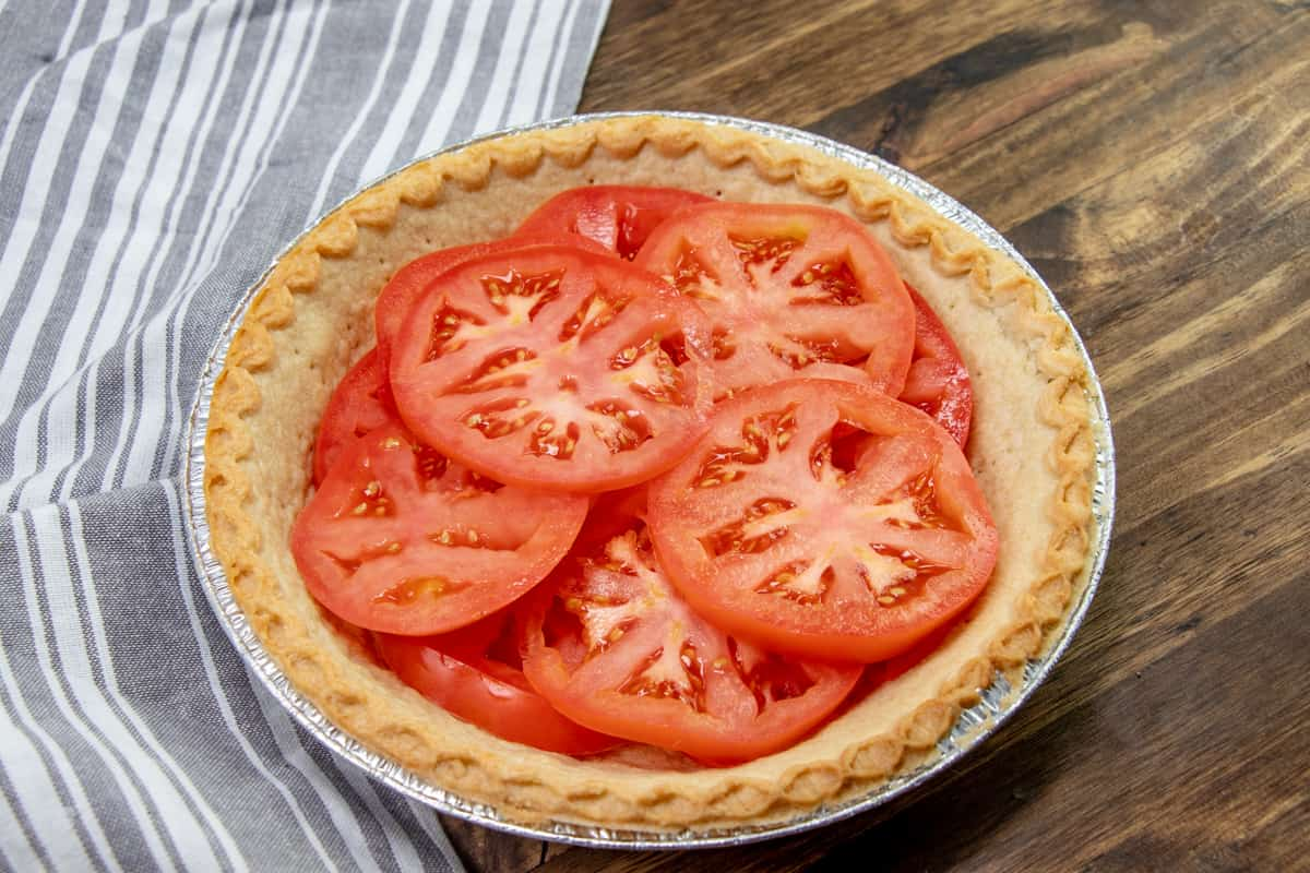 slices of tomato layered in a baked pie crust.