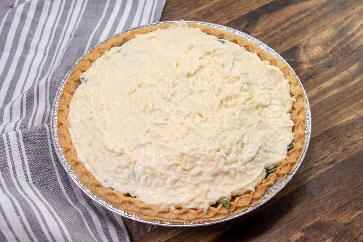 mayonnaise cheese mixture spread out evenly on top of tomato pie.