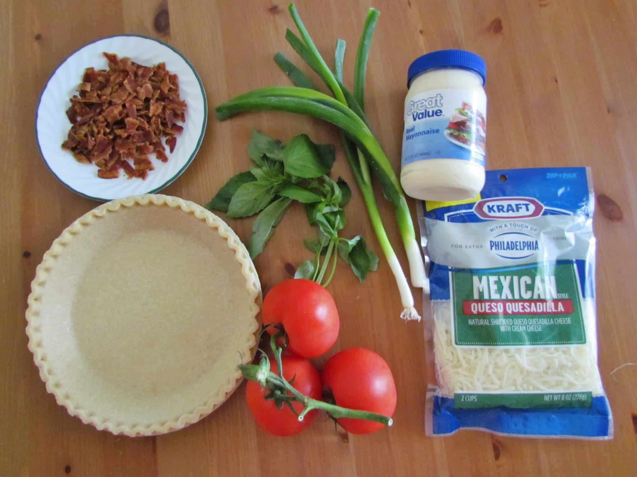 Tomato Pie ingredients: tomatoes, 9-inch frozen pie crust, green onions, basil, chopped bacon, freshly ground black pepper, mayonnaise, shredded mozzarella cheese.