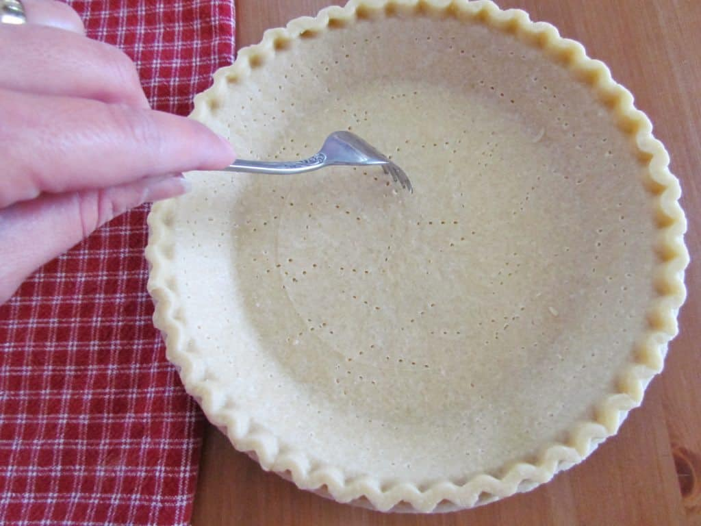 using a fork to poke holes in a frozen pie crust