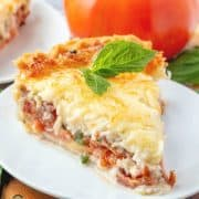Tomato and Bacon Pie topped with melted mozzarella served on a white plate with a sprig of basil on top