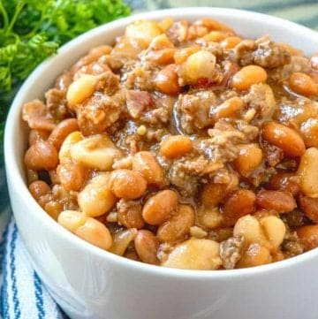 Calico Baked Beans in a white bowl with parsley in the background
