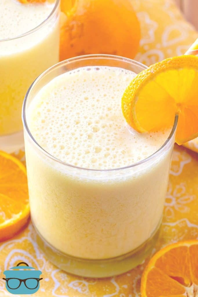 Copycat Orange Julius Drink in a clear glass with a slice of orange