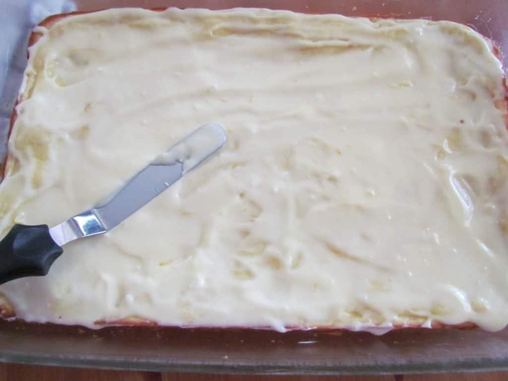 spreading sweetened cream cheese as lemon bar topping