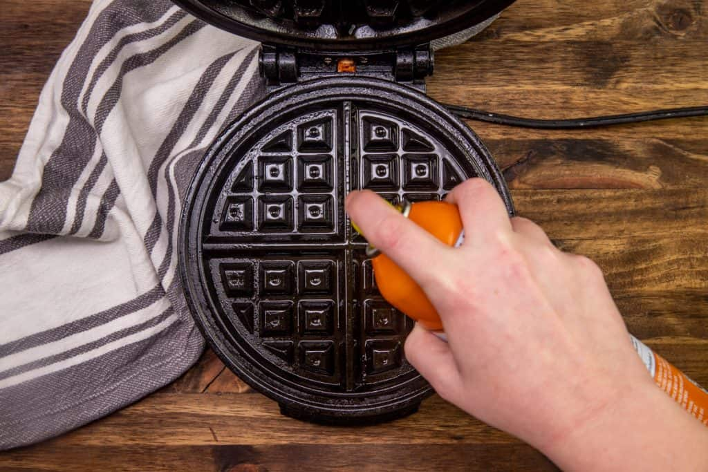 spraying the insides of a waffle maker with nonstick cooking spray