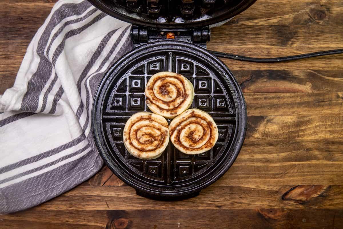 three refrigerated cinnamon rolls on a waffle maker.