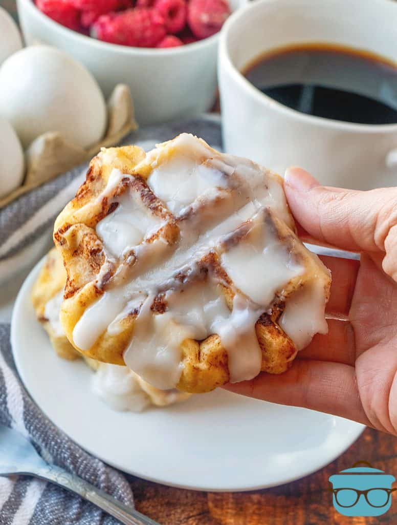 a cinnamon roll waffle being held in a hand with a cup of coffee in the background