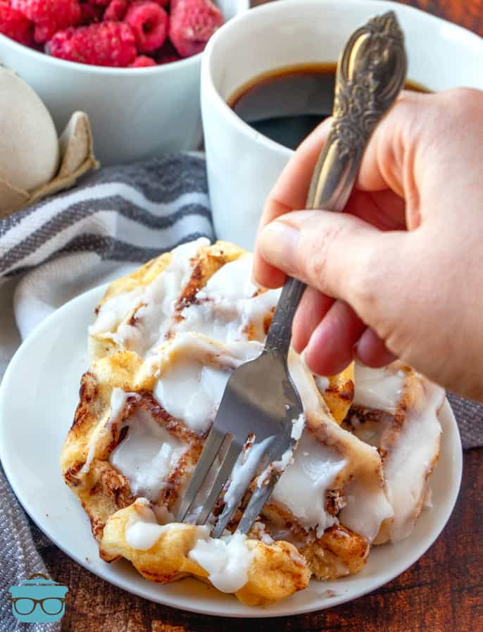 cinnamon roll waffles shown on a small white plate with a fork taking out a piece of the waffle