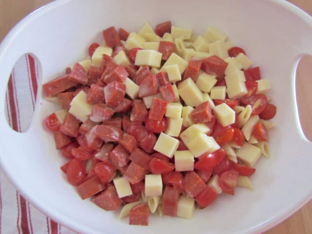 cooled penne pasta, diced mozarella, sliced tomatoes and diced pepperoni in a large bowl