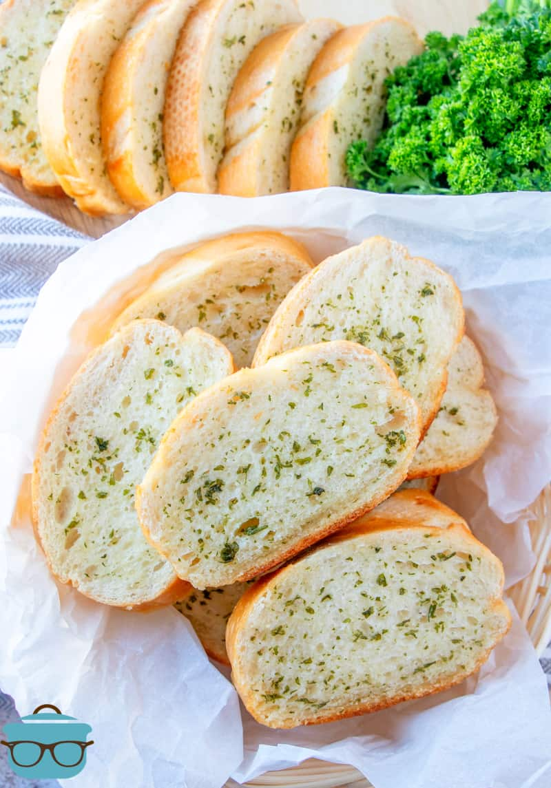 several slices of garlic bread shown in a basket that is lined with white parchment paper